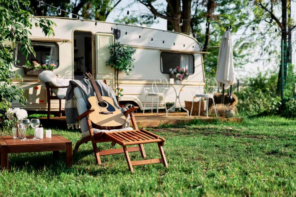 A travel trailer parked on a camping ground with chairs set up outside