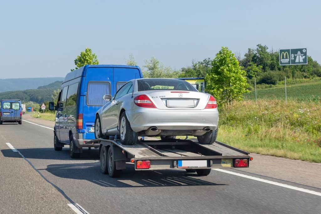 A van towing a Mercedes on the highway