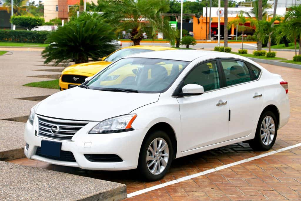 A white Nissan Sentra parked on a parking lot