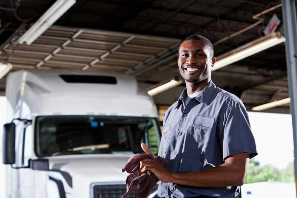 African American man (20s) in service garage repairing semi-truck