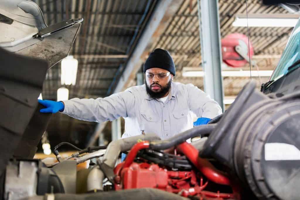 An African-American man in his 30s repairing a semi-truck