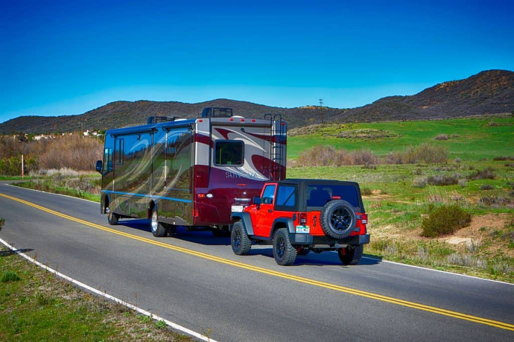 An RV towing a Jeep Wrangler on the road
