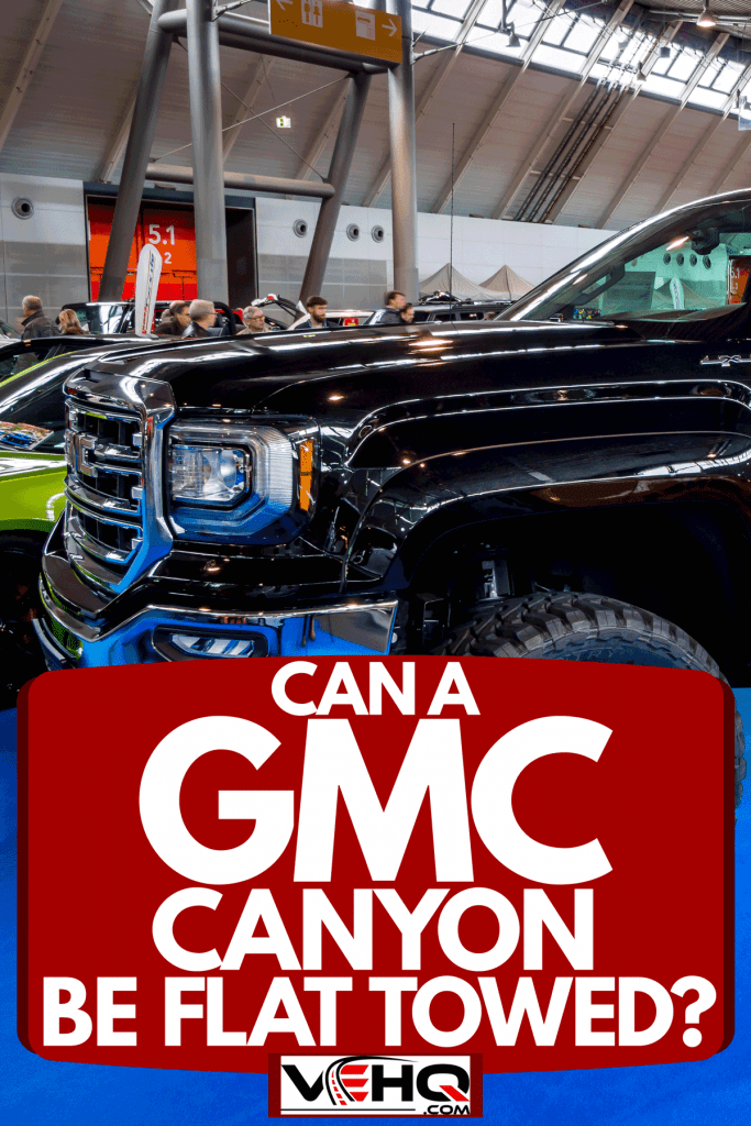 A GMC truck with huge 22 inch tires and a modified lifted chassis displayed at a car show, Can A GMC Canyon Be Flat Towed?