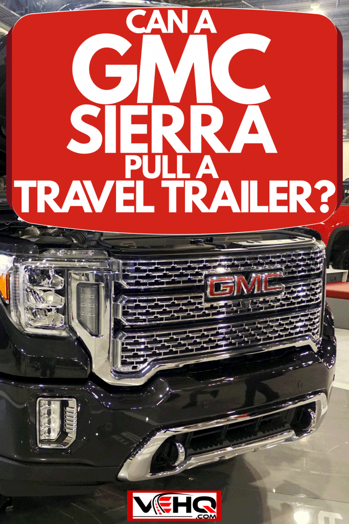 A huge dual rear GMC Sierra 3500 HD with an opened hood and doors displayed at a car show, Can A GMC Sierra Pull A Travel Trailer?