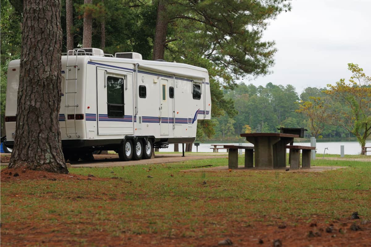 Fifth wheel camper in campground by lake and the woods