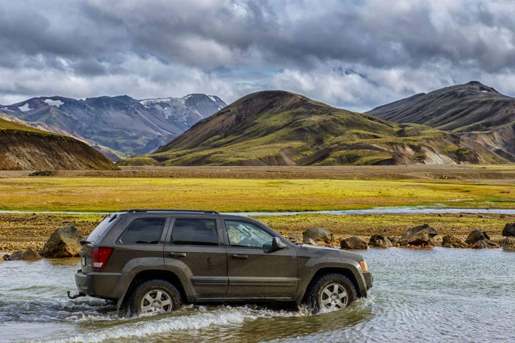 Jeep Grand Cherokee 4x4 SUV driving into a river