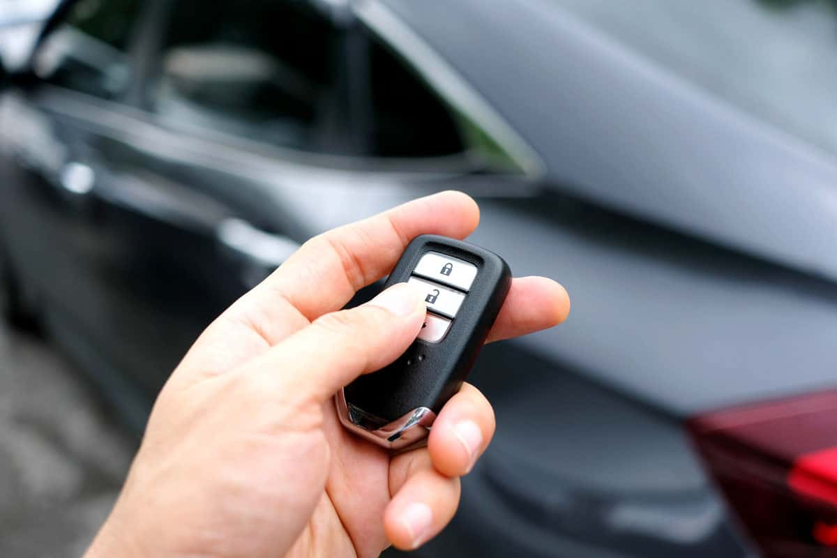 Man hand holding the car remote, he push the remote control to open the car door