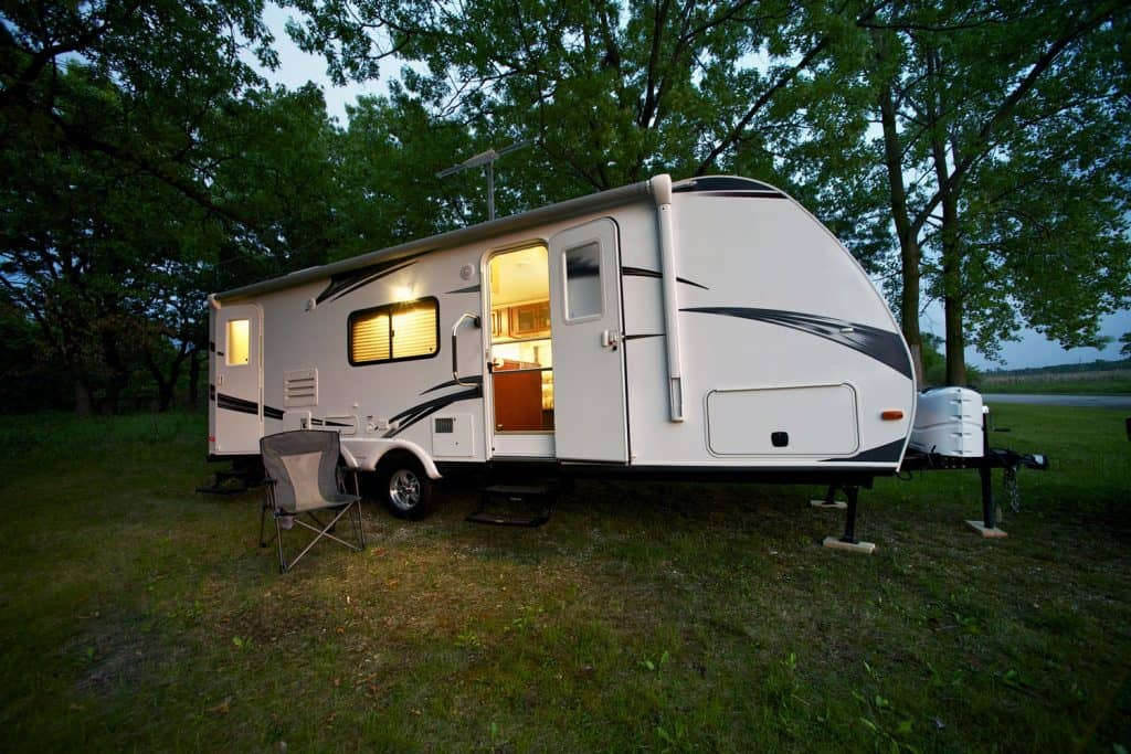 Modern 25 Feet Travel Trailer - Camping in the Forest.