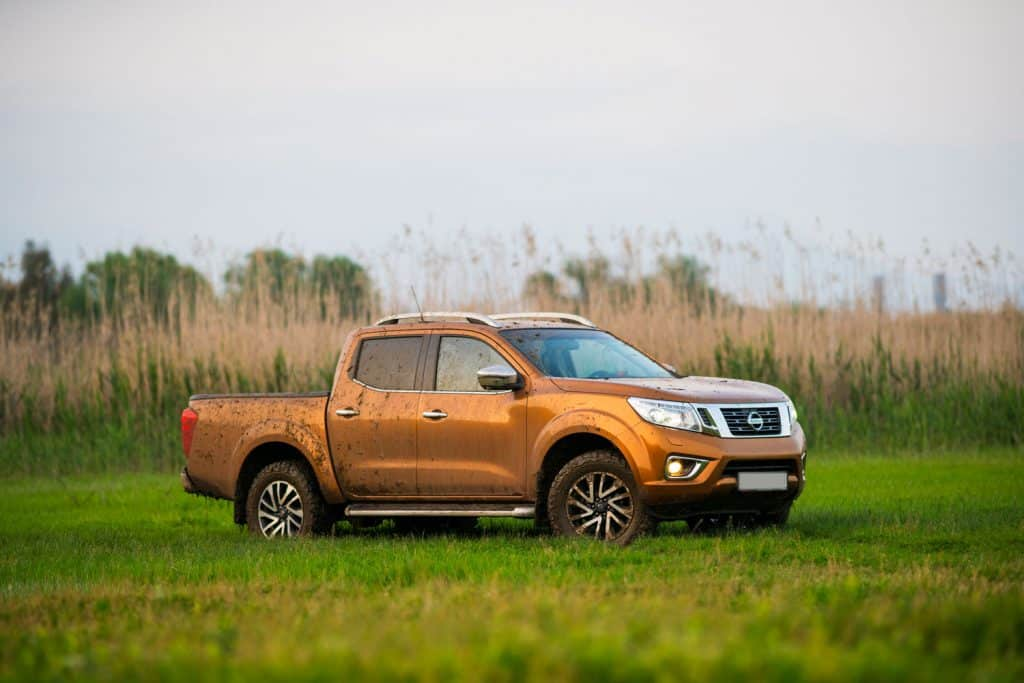 Nissan-Frontier-Pickup-Truck-parked-at-lawn-under-a-big-tree,-near-covered in mud