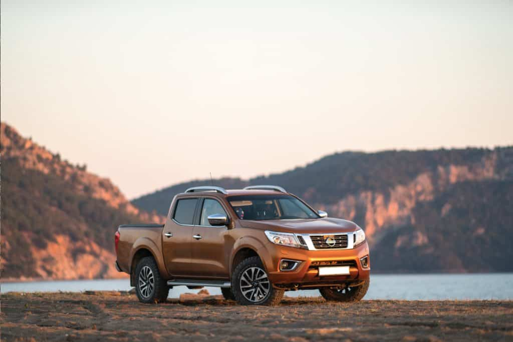 Nissan NP300 Frontier stopped on the beach, How Long Is A Nissan Frontier? (For Various Bed Lengths)