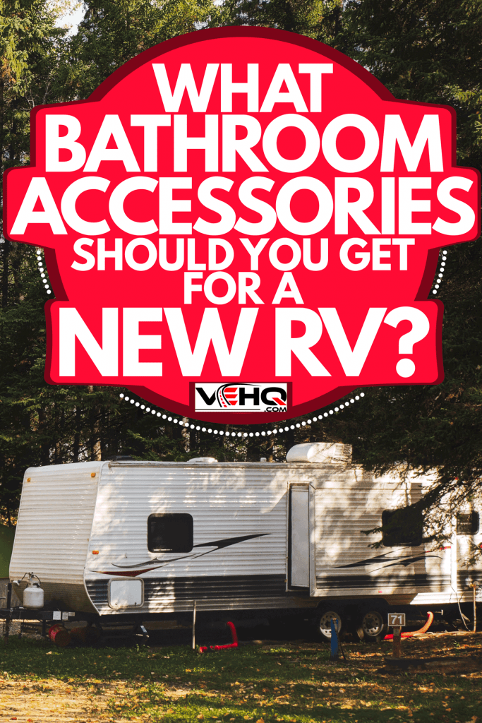 A fifth wheel parked on a pine tree forest with tents set up outside, What Bathroom Accessories Should You Get For A New RV?