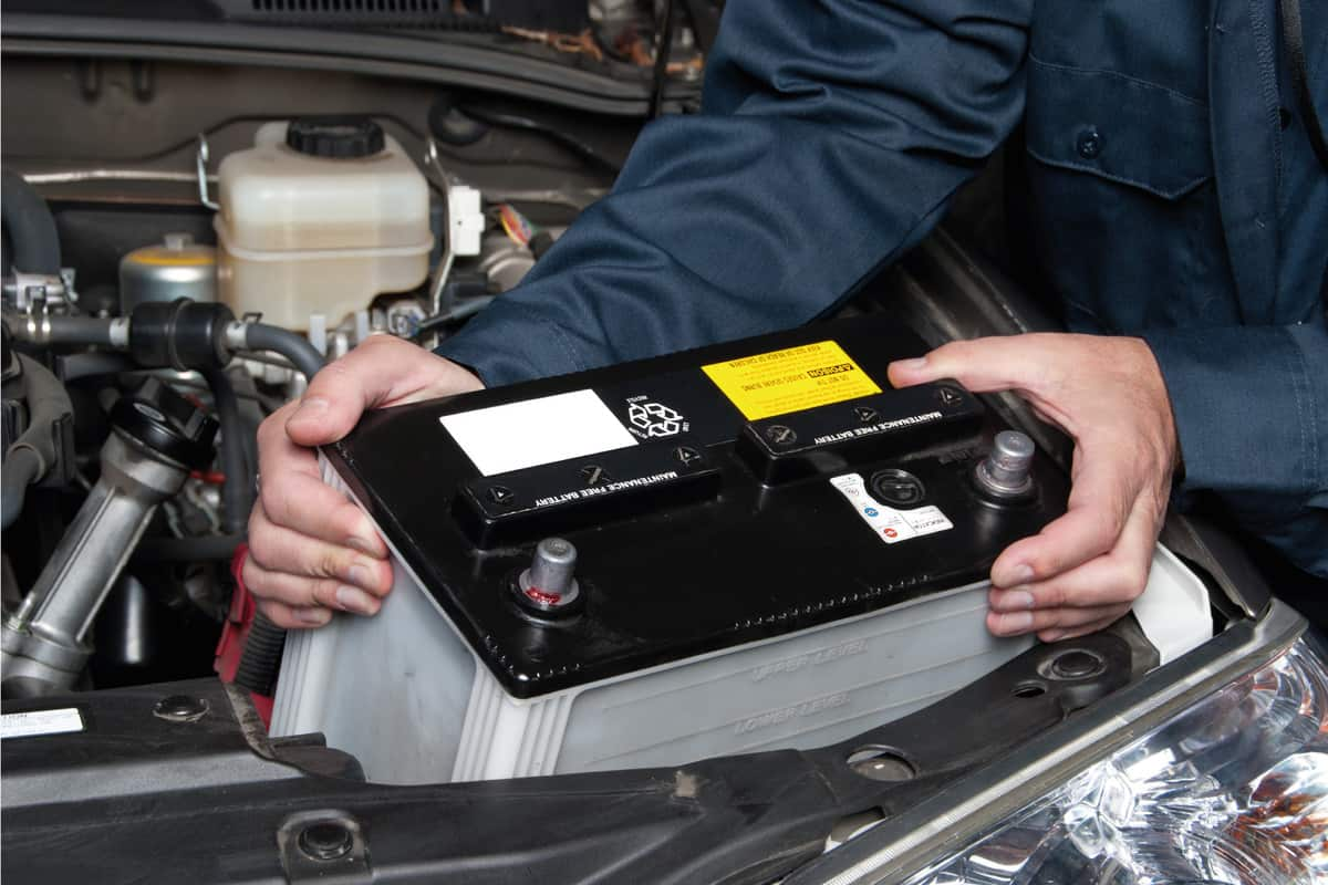 Car battery being loaded into the engine bay by a mechanic