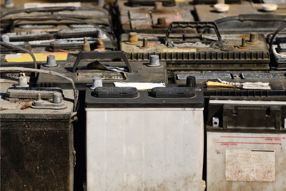 Old car batteries piled upright in a stocking facility