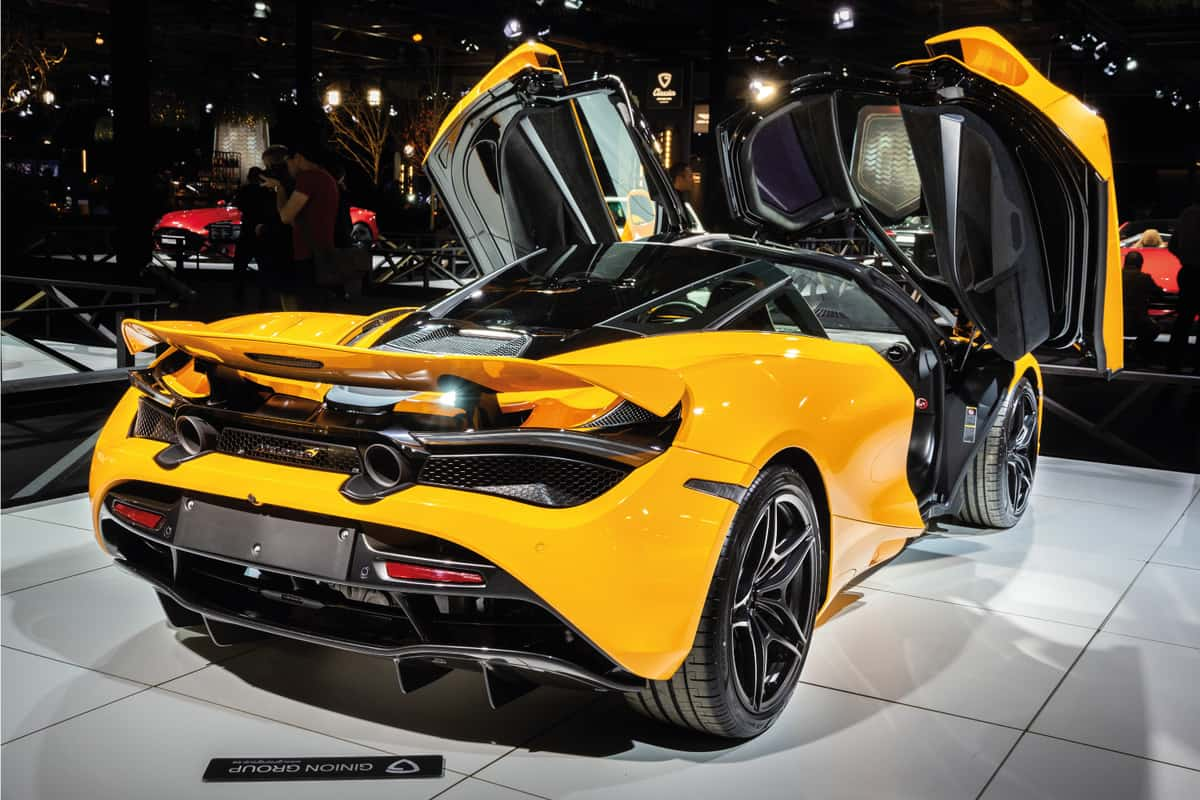 Photo from behind of a McLaren 720S sports car with butterfly doors on a car show