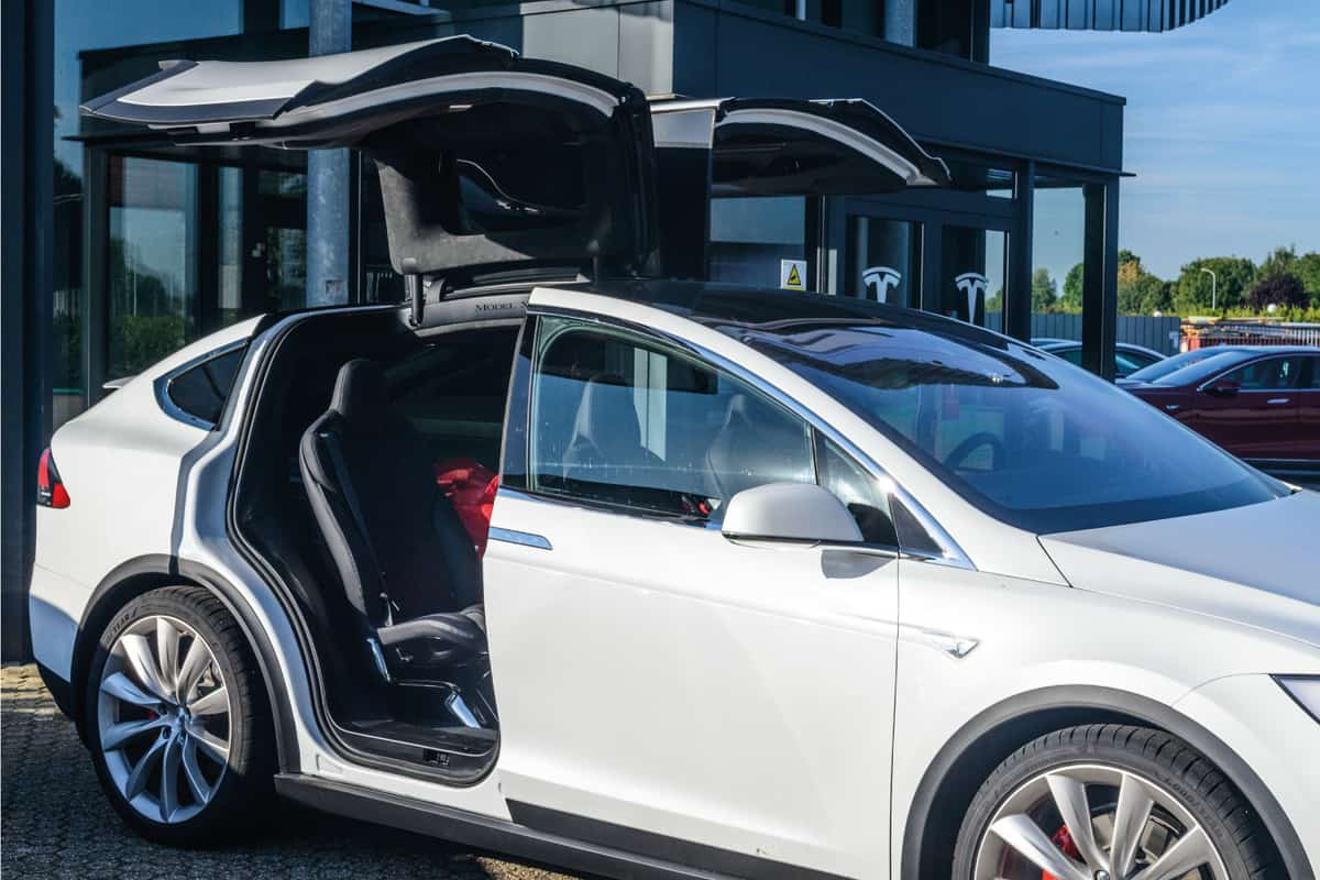 White Tesla Model X with opened gull wing and falcon doors at a Tesla dealership