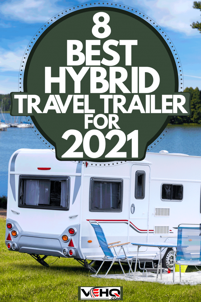 A travel trailer parked on the side of a lake providing a panoramic view of the lake and forest trees, 8 Best Hybrid Travel Trailers For 2021
