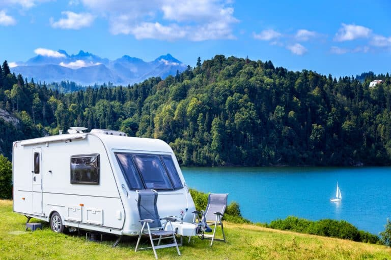 A camper van parked near a beautiful lake with a panoramic view of the mountains and vegetation, 8 Travel Trailers That Can Fit In Your Garage