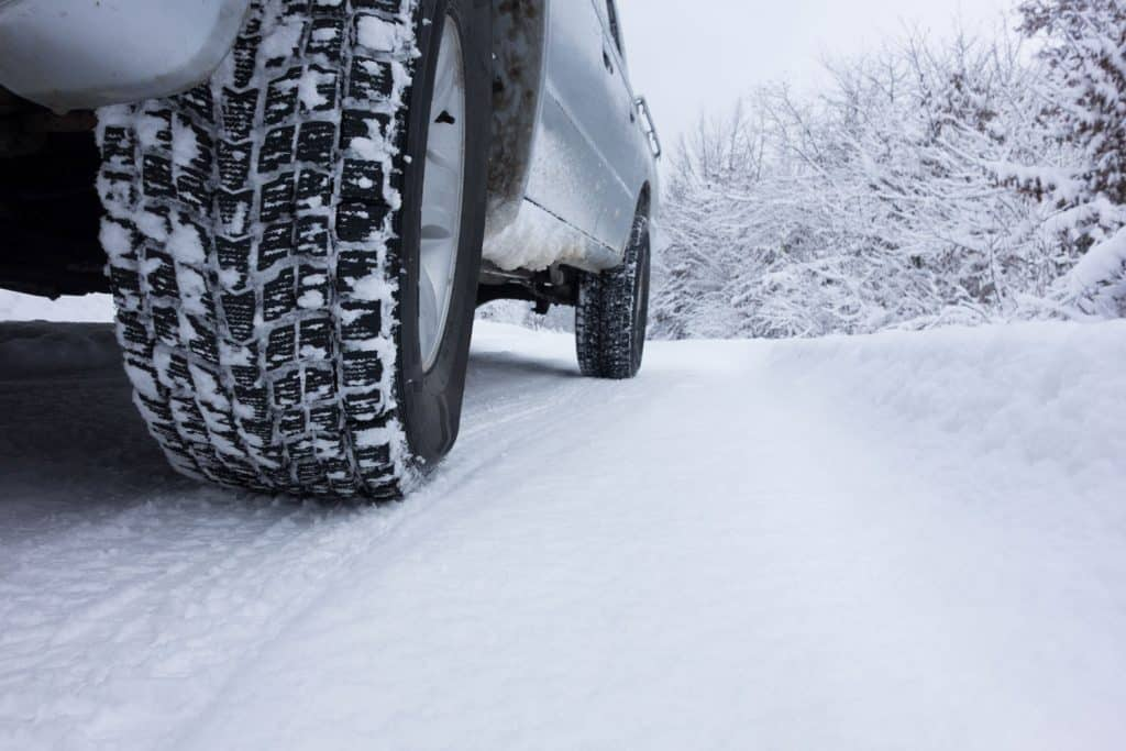 A detailed view of a trucks winter tyre moving on the snow