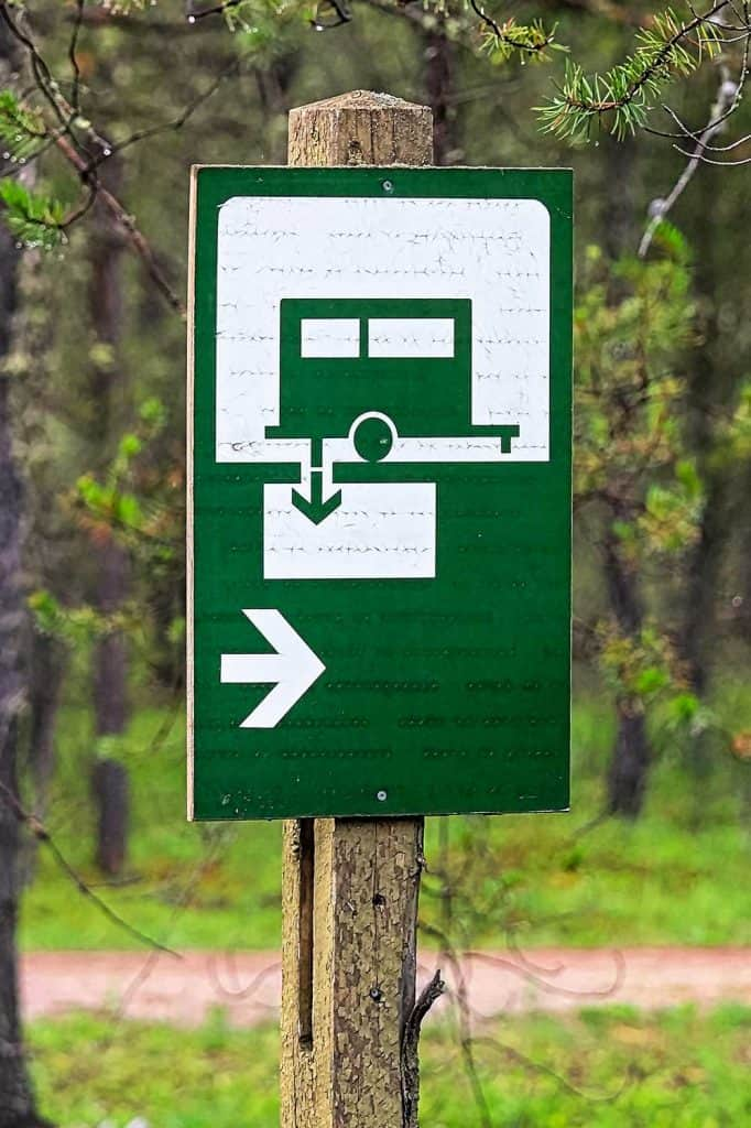 A green sani-dump sign with a direction arrow