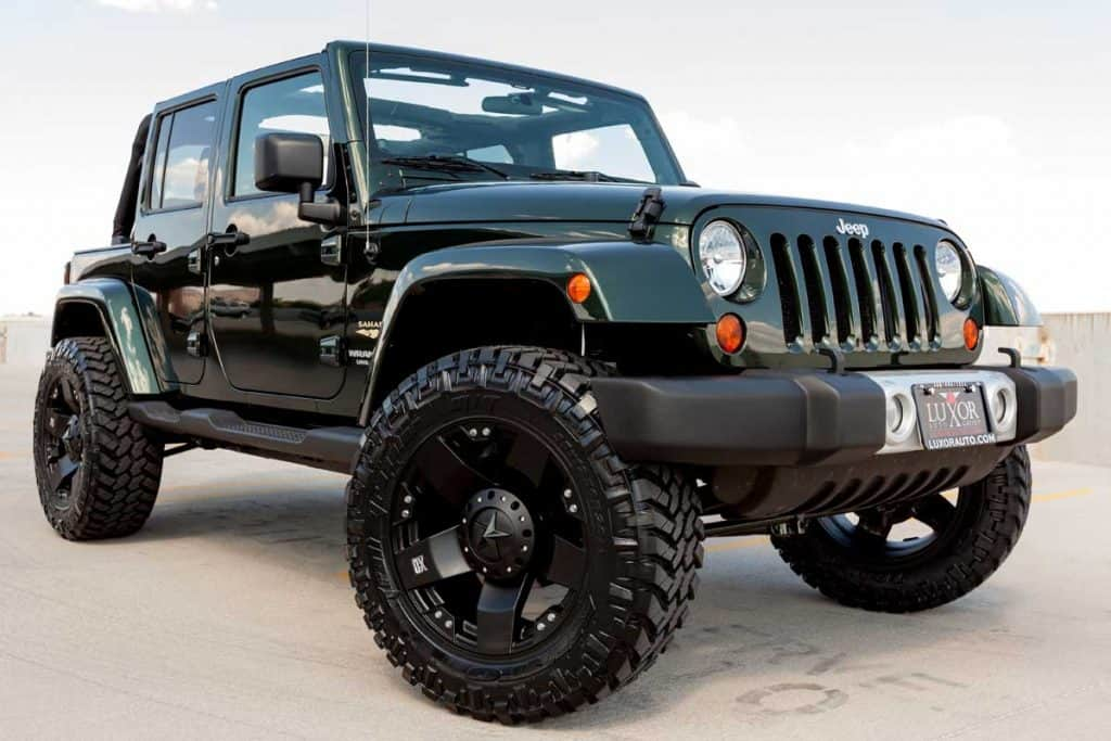 A parked green Jeep Wrangler with custom lift kit and wheels, How Much Does It Cost To Re-gear A Jeep?