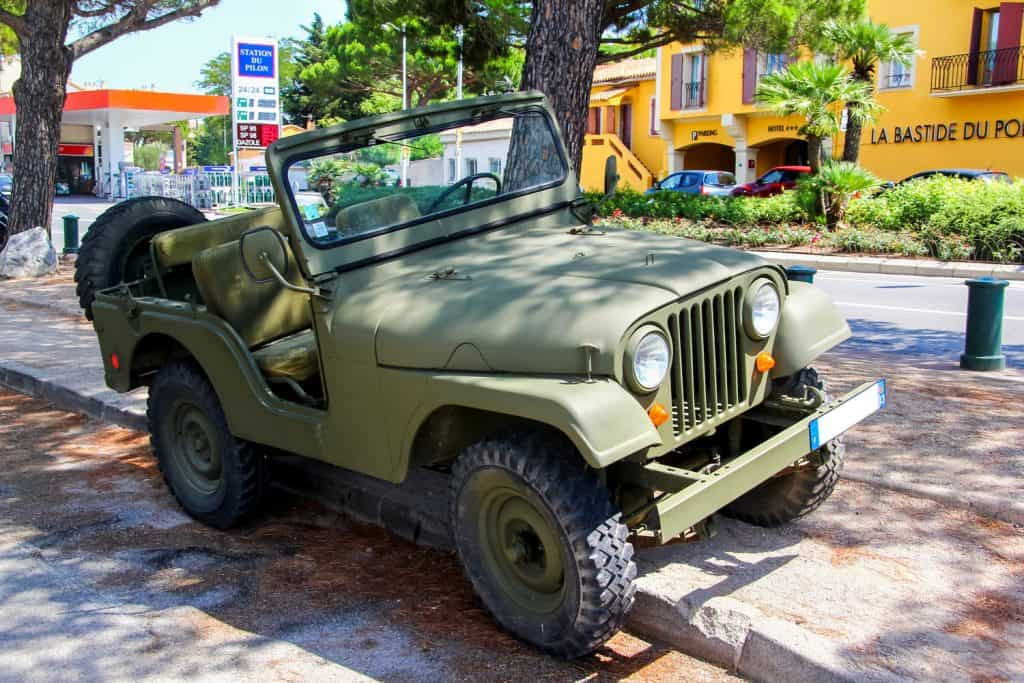 A vintage CJ-5 jeep parked on the side of a street