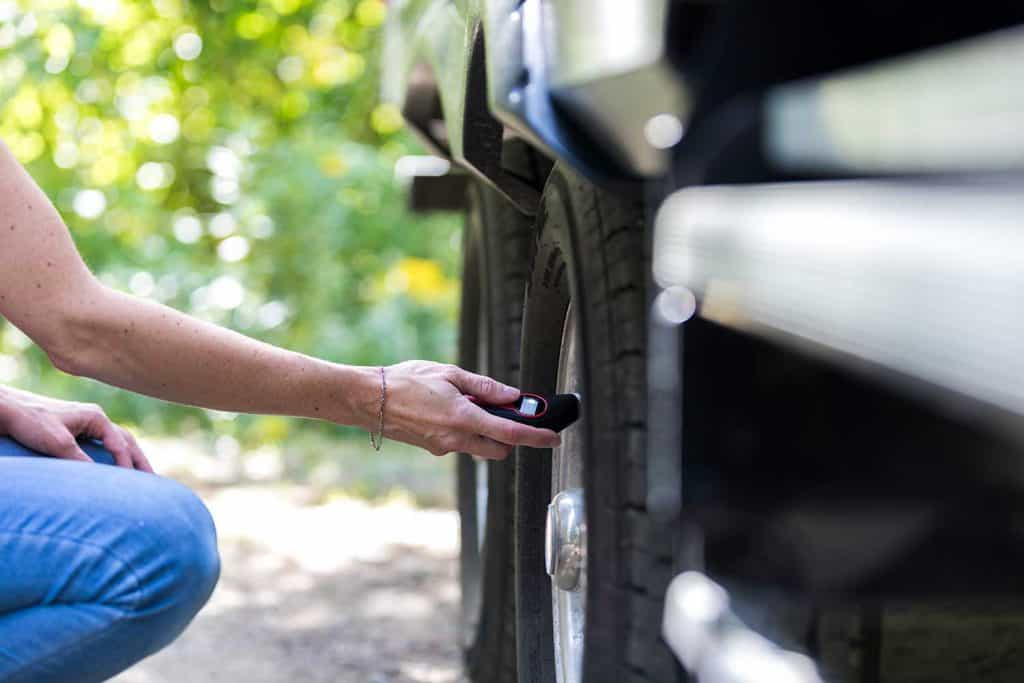 A woman is verifying the tire pressure of her camper trailer before leaving campground