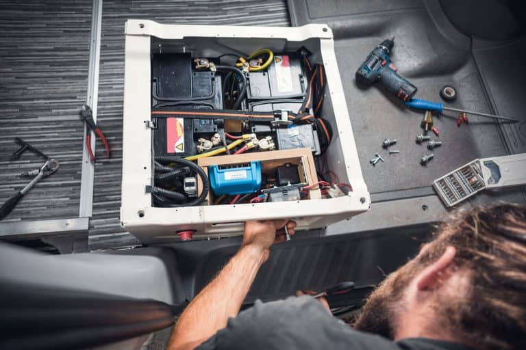 Bearded man working on a DIY camper van. He is working on the base of a front seat to install additional batteries, How Long Will An RV Battery Last (Inc. When Dry Camping)?
