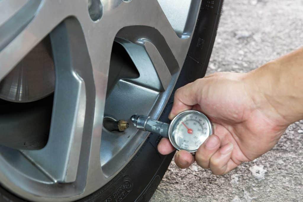Car tire pressure check using air pressure gauge