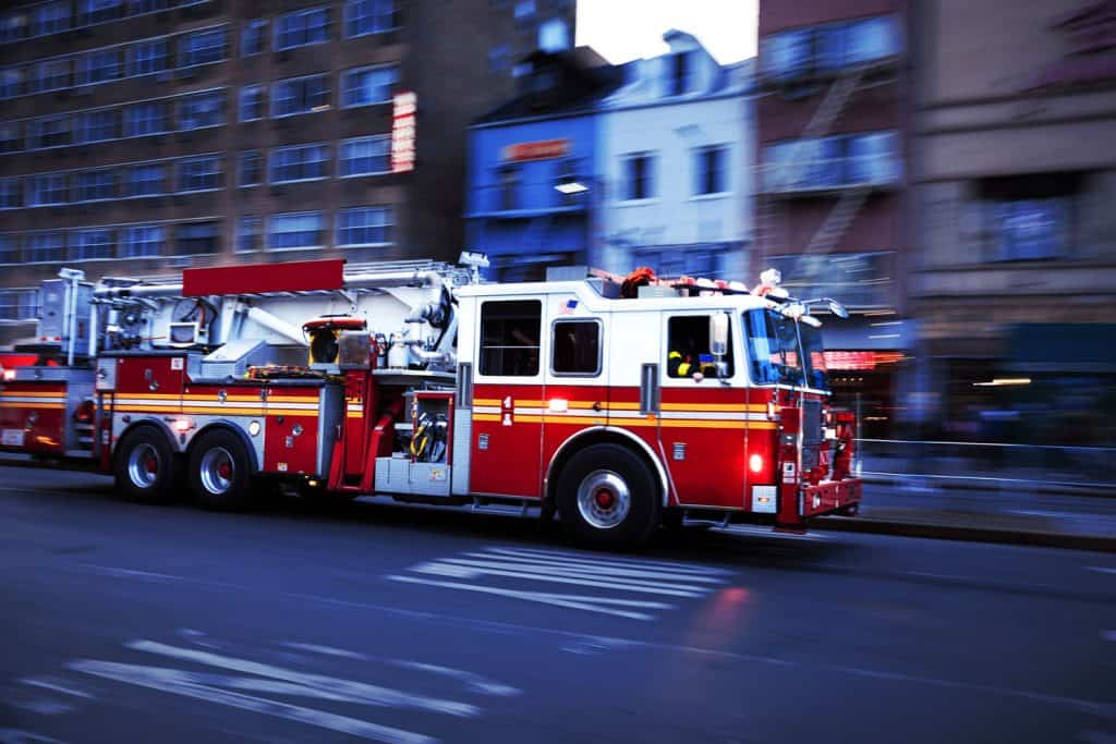 A firetruck travelling to the scene of accicdent, Why Are Fire Trucks Red? [Amazing Facts and Myths!]