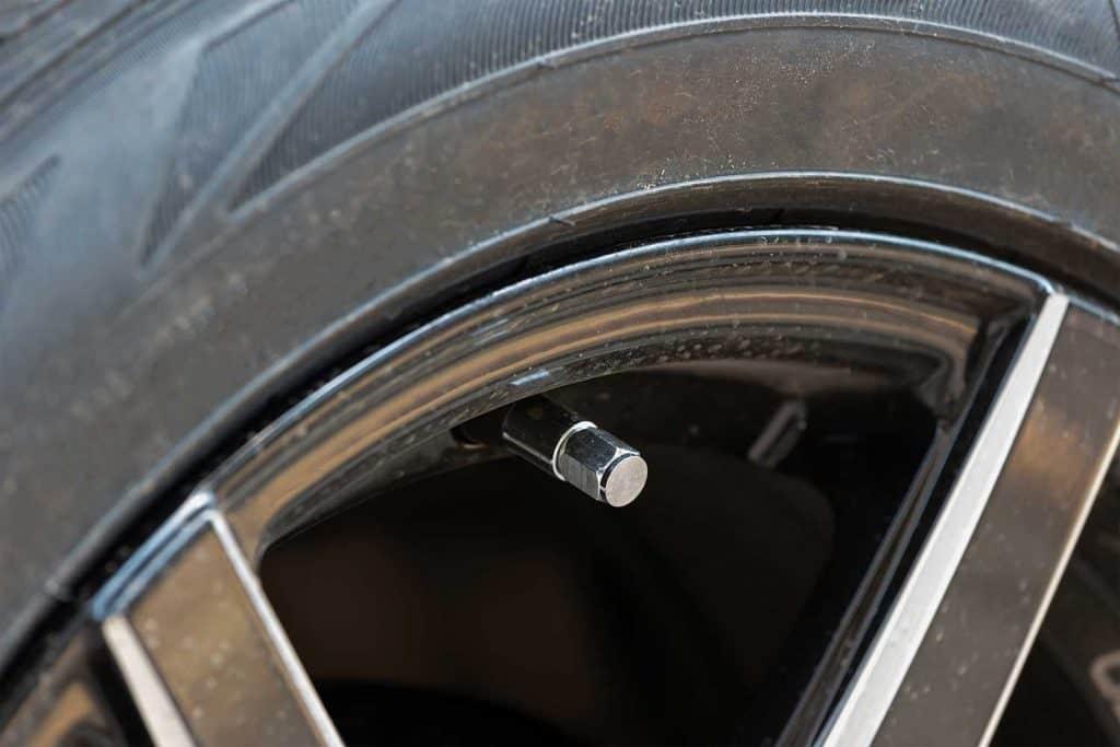 Metal tire valve on car wheel