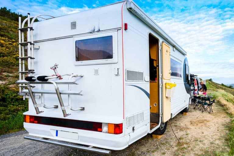 Motorhome RV and campervan are parked on a beach, How To Anchor Down An RV [4 Great Options]