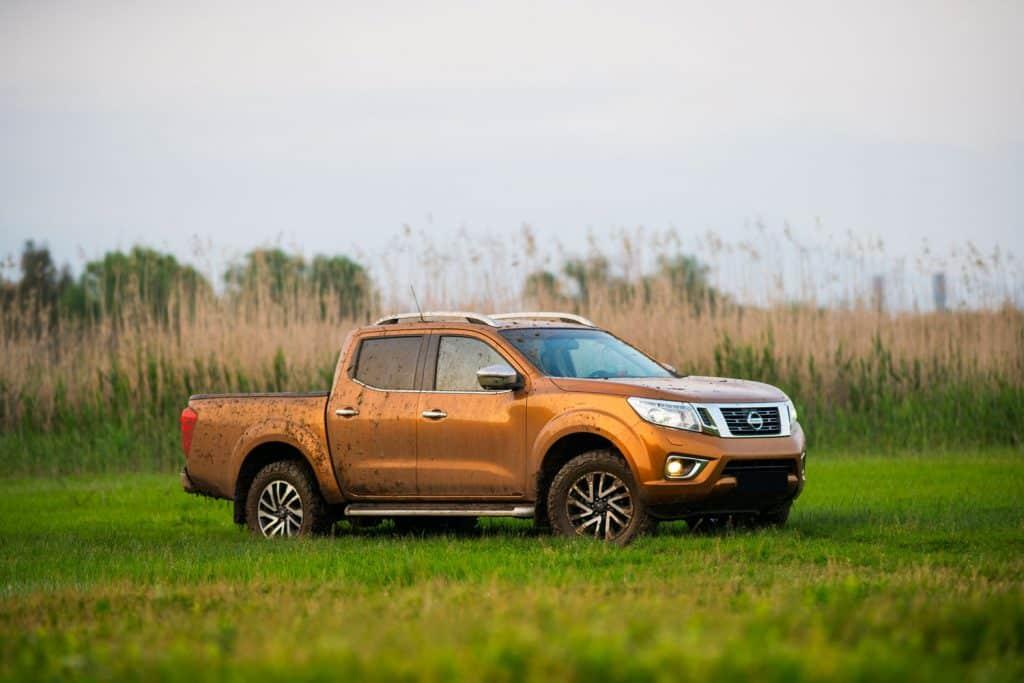 A Nissan Frontier pickup truck trekking on a muddy field
