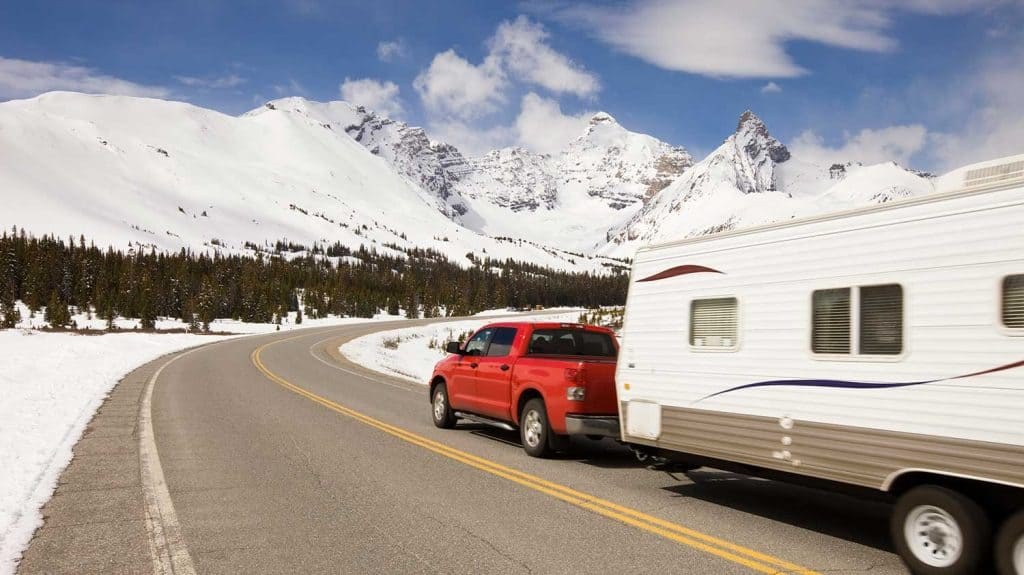 Pickup truck and travel trailer passing by on a highway in the mountains