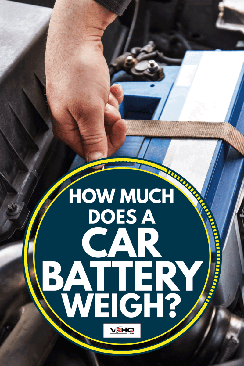 Car mechanic tightening the nut and bolt of car battery mount in the engine bay, How Much Does A Car Battery Weigh?