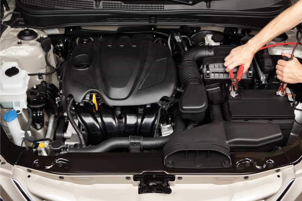 Car mechanic using jumper cables on a car battery in the engine bay of a car, How Much Does A Car Battery Weigh?