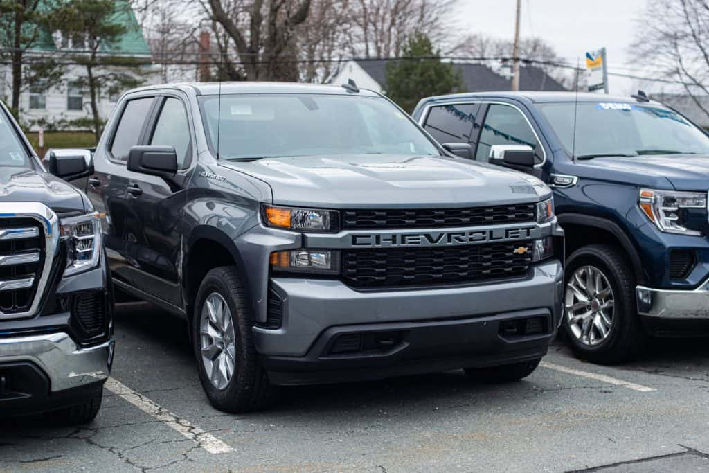 A huge gray colored Chevrolet Silverado parked outside a parking lot, What Are the Biggest Tires You Can Fit On A Chevy Silverado?
