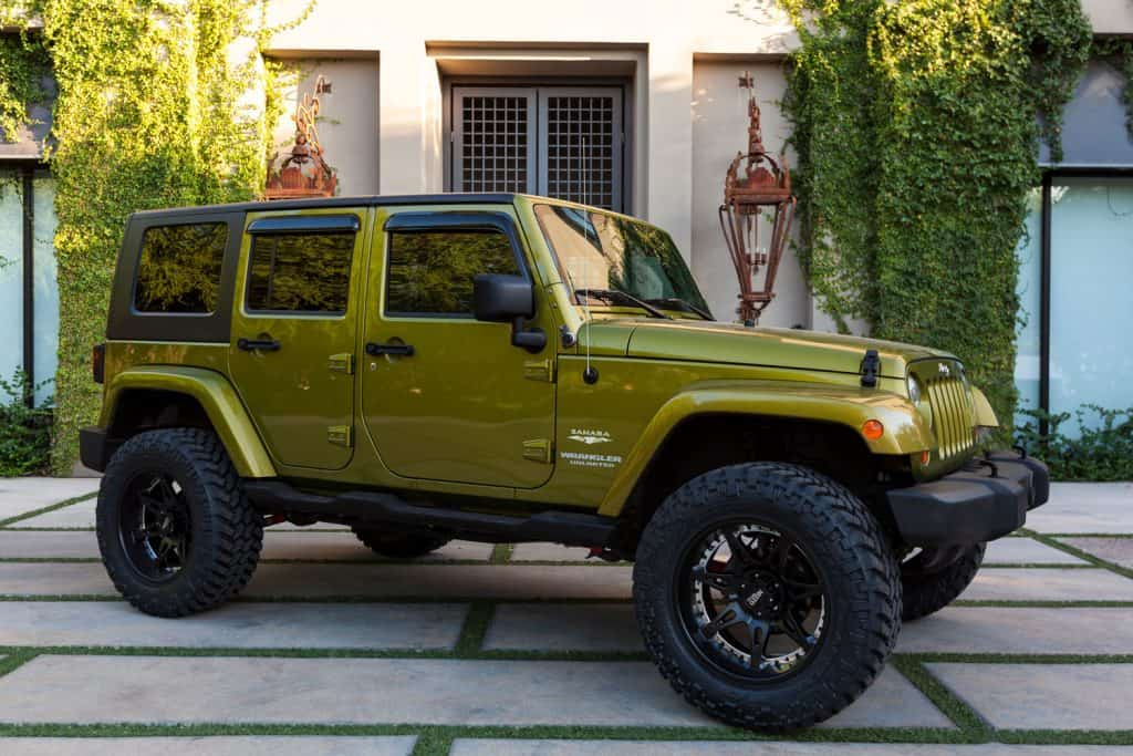 A light yellow green colored Jeep Wrangler parked outside a house