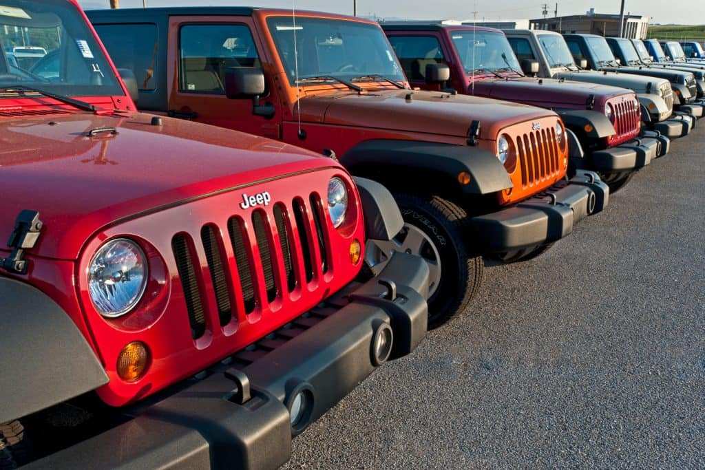 Different colored Jeep Wranglers outside a car dealership