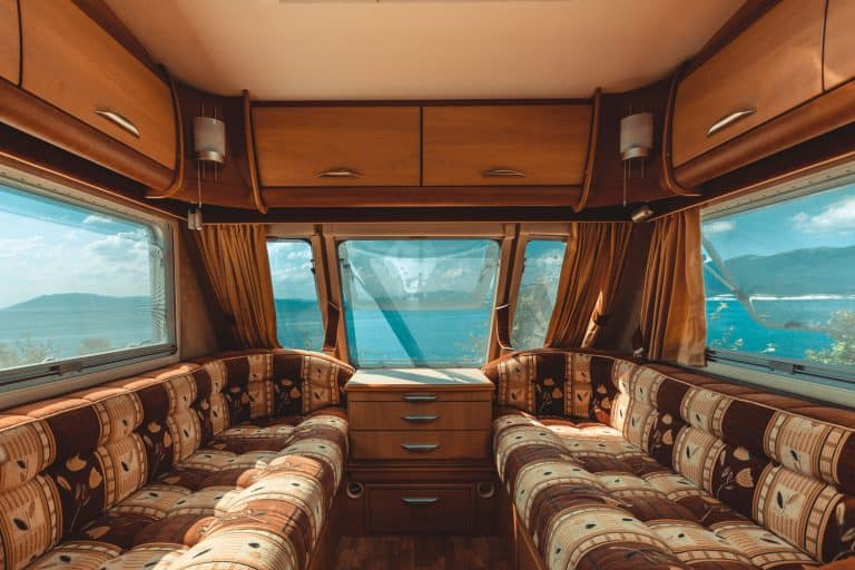 Interior of a rustic themed caravan with long sofas, a center table, and overhead cabinets with overlooking windows, How To Seal RV Windows To Stop Leaks