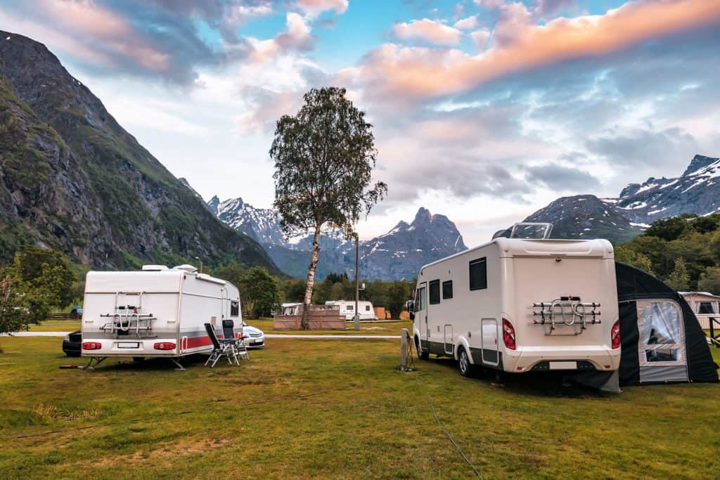 Two RVs parked outside a camping ground with a panoramic view of the mountain range, RV Water Pump Runs But No Water - What To Do?