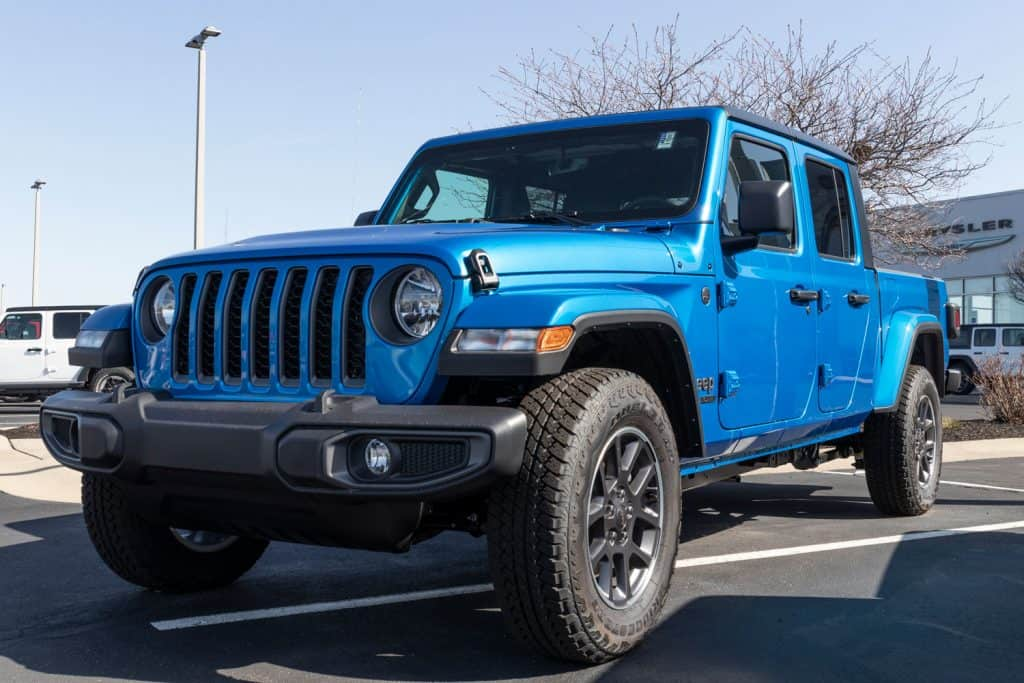 A Jeep Gladiator parked outside a Chrysler dealership, Why Are Jeeps So Expensive? [And Yet Popular]