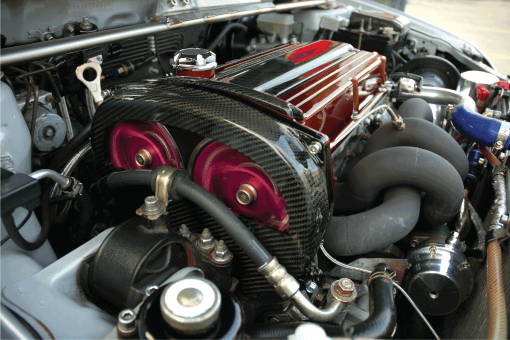 A modified motor running under the hood of a sports car. 5.7 Hemi Engine Burning Oil - What To Do