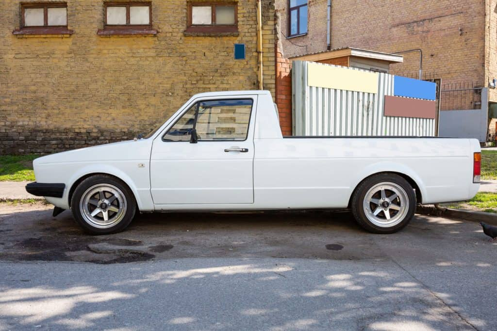 A white long Volkswagen truck parked outside an apartment