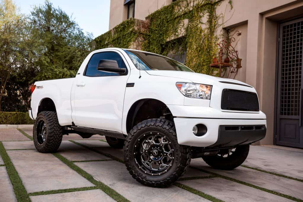 An old version of a Toyota Tundra parked outside a mansion
