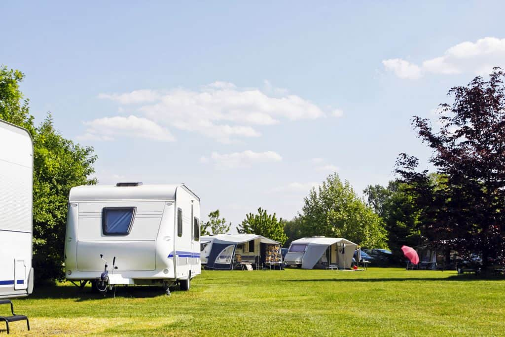 Camper trailers lined up outside a camping ground