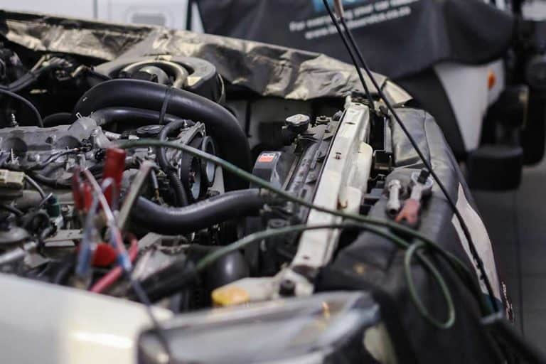 Diesel technicians working on an engine in an auto repair shop, Is Propane Injection For Diesels Worth It? [A Thorough Discussion]