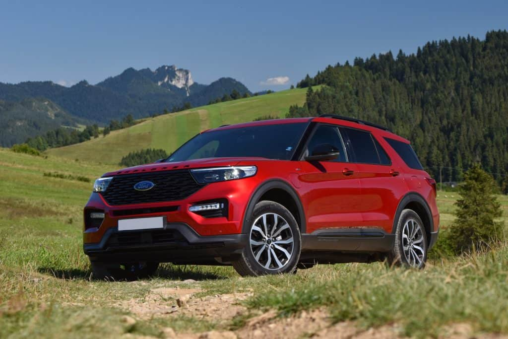Ford Explorer V6 Plug-in Hybrid stopped on a road in mountain scenery. Rapid Red