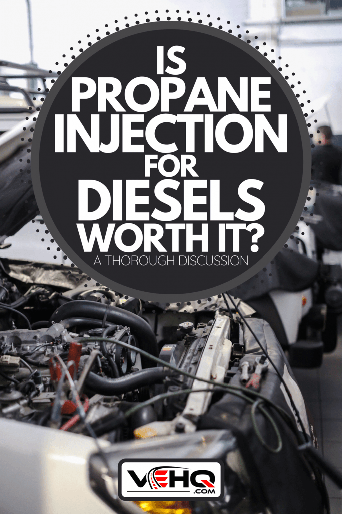 A diesel technicians working on an engine in an auto repair shop, Is Propane Injection For Diesels Worth It? [A Thorough Discussion]
