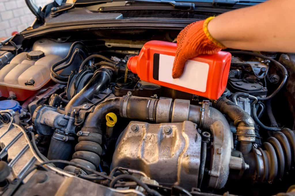 Oil change in car service. Hand in protective glove with oil bottle, 7 Of The Best Oil Additives For Older Engines