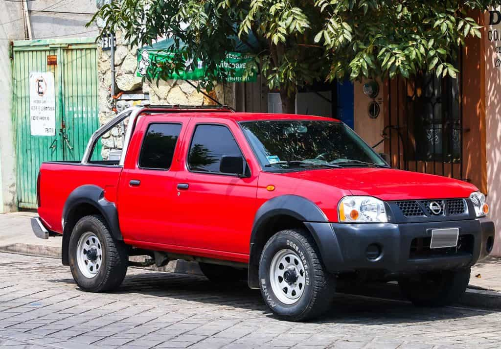 Red pickup truck Nissan Frontier in the city street